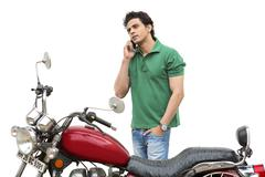 Man standing beside a motorcycle and talking on a mobile phone - stock photo