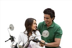 Couple looking at each other and smiling while riding a motorcycle - stock photo
