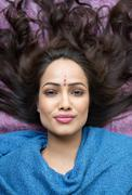 Portrait of a woman lying down and smiling - stock photo