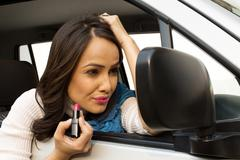 Woman applying lipstick on her lips while sitting in a car Stock Photos