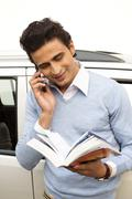 Man standing outside his car and talking on a mobile phone Stock Photos