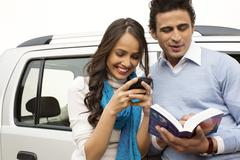 Woman text messaging with a mobile phone and man reading a book Stock Photos