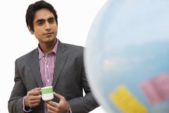 Businessman holding a tea cup and looking at a globe - stock photo