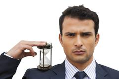 Portrait of a businessman holding an hourglass - stock photo