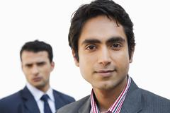 Close-up of a businessman smiling with his colleague in the background - stock photo