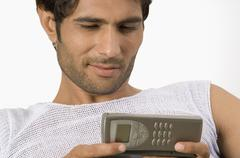 Close-up of a man text messaging on a mobile phone - stock photo