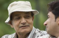 Close-up of a man with his father in a park Stock Photos