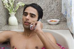Man relaxing in the bathtub and talking on a mobile phone Stock Photos