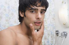 Portrait of a man touching his face after shave Stock Photos
