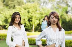 Two women posing in a park - stock photo