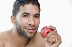 Portrait of a macho man eating apple Stock Photos