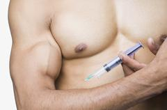Close-up of a macho man taking steroids - stock photo