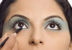 Person's hand applying eye liner on a young woman Stock Photos