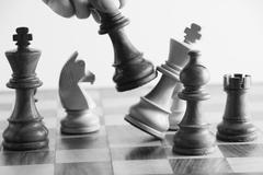 Person's hand defeating a king in the game of chess Stock Photos