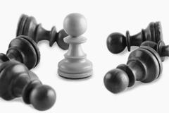 White chess pawn surrounded by black chess pawns Stock Photos