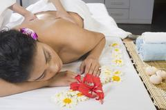 Young woman getting back massage from a massage therapist - stock photo