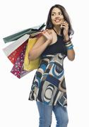 Young woman holding shopping bags and talking on a mobile phone - stock photo
