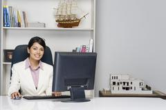 Portrait of a businesswoman working on a desktop PC in an office Stock Photos