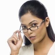 Portrait of a curious businesswoman holding her eyeglasses - stock photo