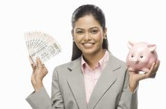 Portrait of a businesswoman showing Indian paper currency and a piggy bank - stock photo