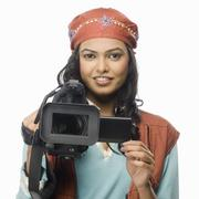 Portrait of a female videographer videographing - stock photo