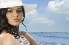 Portrait of a female fashion model posing on the beach - stock photo