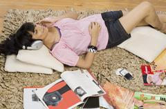 Young woman listening music in a living room Stock Photos