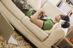 Young man lying on a couch and listening to music Stock Photos