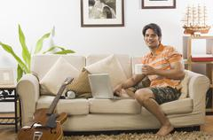 Young man holding a coffee mug in the living room - stock photo