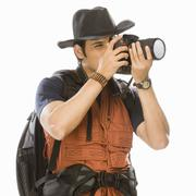 Young male photographer photographing with a digital camera Stock Photos