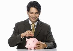 Stock Photo of Businessman putting a coin into a piggy bank