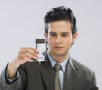 Businessman looking at an hourglass - stock photo