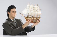 Businessman looking at a model ship - stock photo