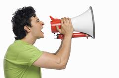 Man holding a megaphone and shouting Stock Photos