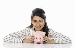 Portrait of a businesswoman holding a piggy bank - stock photo
