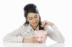 Stock Photo of Businesswoman inserting a coin into a piggy bank