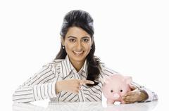 Portrait of a businesswoman pointing towards piggy bank Stock Photos