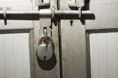 Close-up of a door locked with a padlock - stock photo