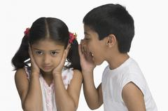 Girl covering her ears while her brother shouting Stock Photos