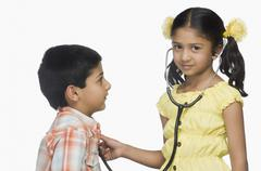 Portrait of a girl examining a boy with a stethoscope Stock Photos