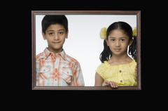 Portrait of a girl and a boy in a picture frame Stock Photos