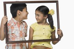 Boy and a girl holding an empty picture frame Stock Photos