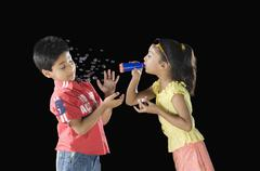Girl blowing bubbles towards a boy Stock Photos