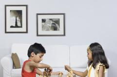 Boy and a girl playing chess Stock Photos