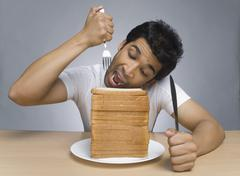 Hungry man eating slices of bread Stock Photos