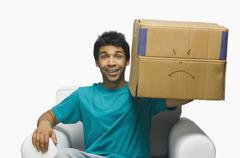 Stock Photo of Man holding a cardboard box and smiling