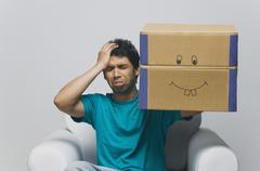 Man holding a cardboard box and looking sad Stock Photos