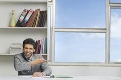 Businessman gesturing and smiling in an office Stock Photos