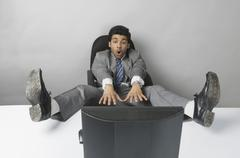 Businessman looking surprised with his feet up in front of a desktop PC Stock Photos