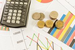 Liike kaaviossa taloudellinen selvitys kolikoilla ja laskin Kuvituskuvat